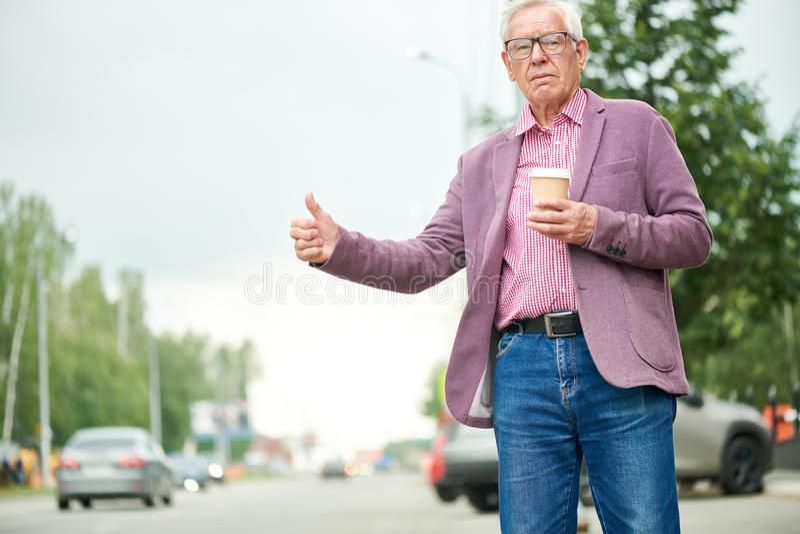 Hombre mayor que llama el taxi fotografía de archivo