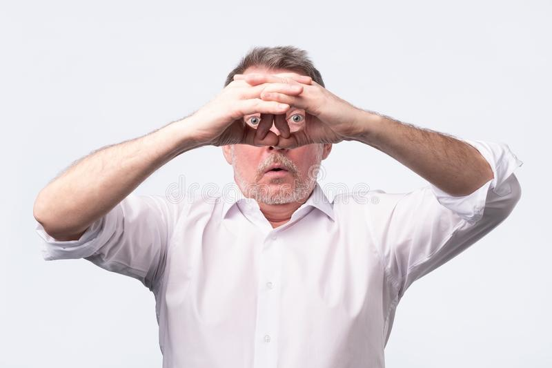 Hombre mayor que lleva a cabo sus manos en sus ojos como si mire a trav?s de los prism?ticos fotos de archivo libres de regalías
