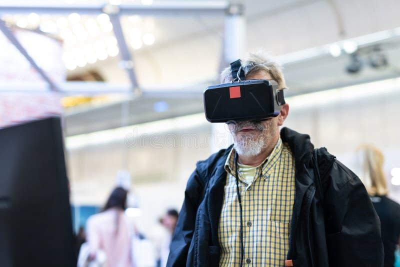 Hombre mayor que lleva las gafas de la realidad virtual que miran la presentación de la realidad virtual fotos de archivo