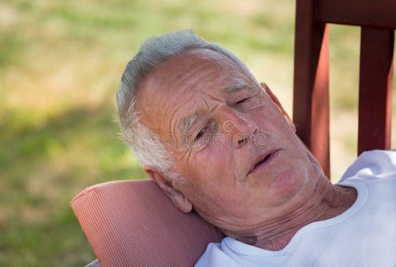 Hombre mayor que miente en banco en jardín fotografía de archivo libre de regalías