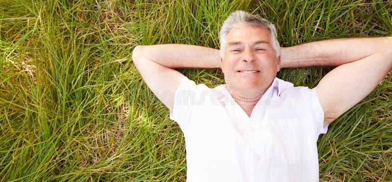 Hombre mayor que miente en la hierba que se relaja fotos de archivo