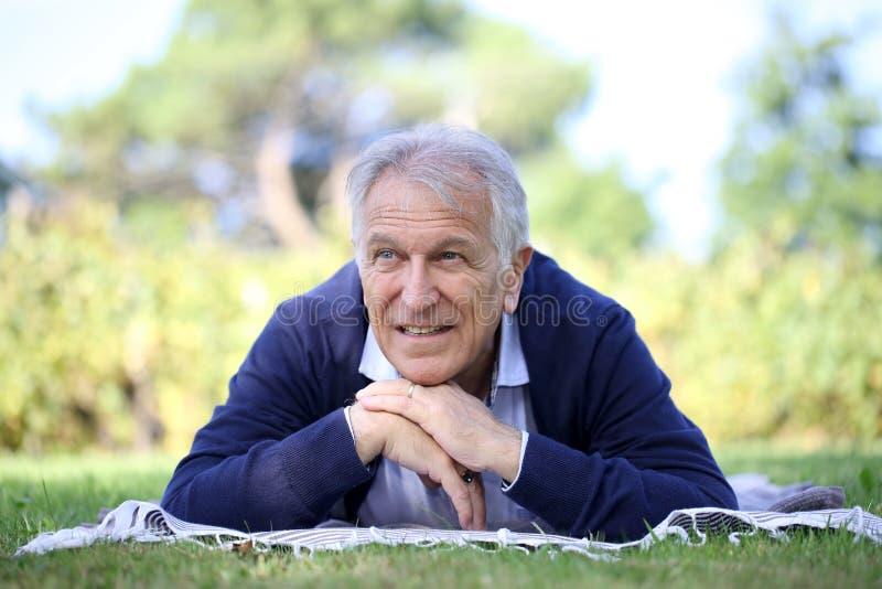 Hombre mayor que miente en la hierba que se relaja imagenes de archivo