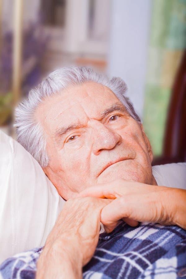 Hombre mayor que miente en malo fotografía de archivo