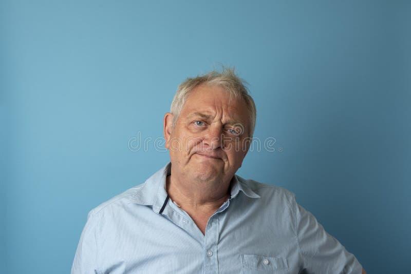 Hombre mayor que mira cansado enfadado imagenes de archivo