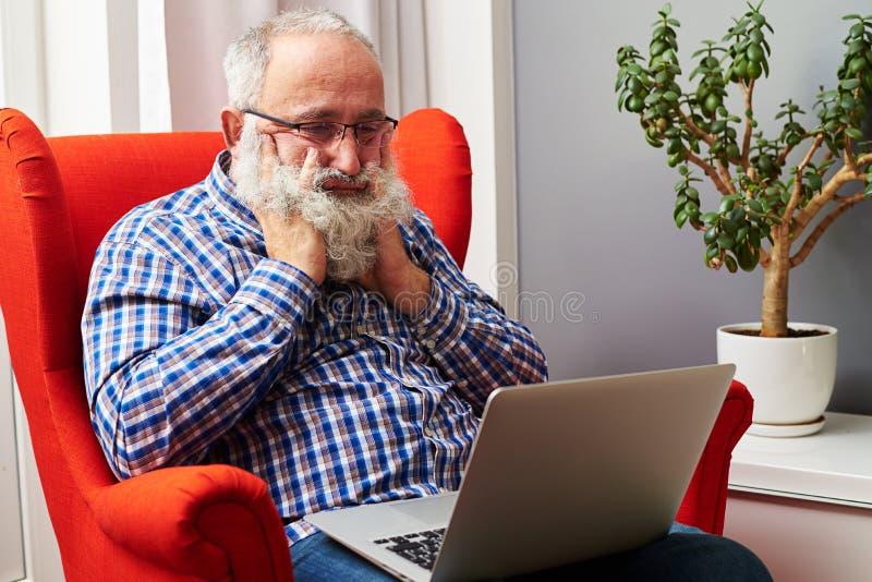 Hombre mayor que mira el ordenador portátil y el taladro en casa imagen de archivo
