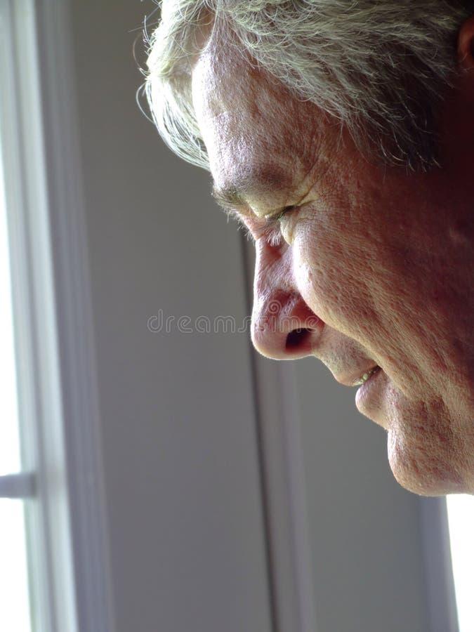 Hombre mayor que mira fuera de una ventana foto de archivo