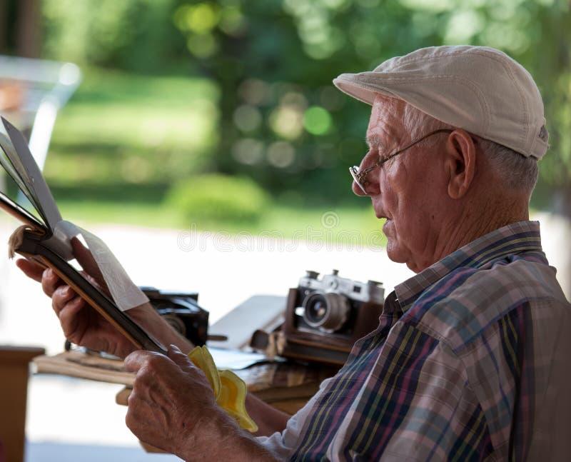 Hombre mayor que mira las fotos viejas imagen de archivo