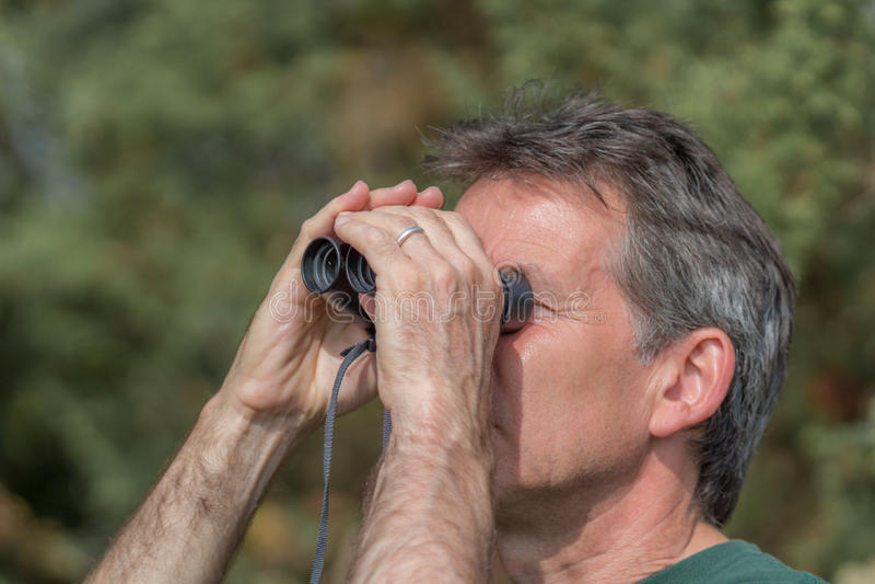 Hombre mayor que mira a través de los prismáticos imagen de archivo
