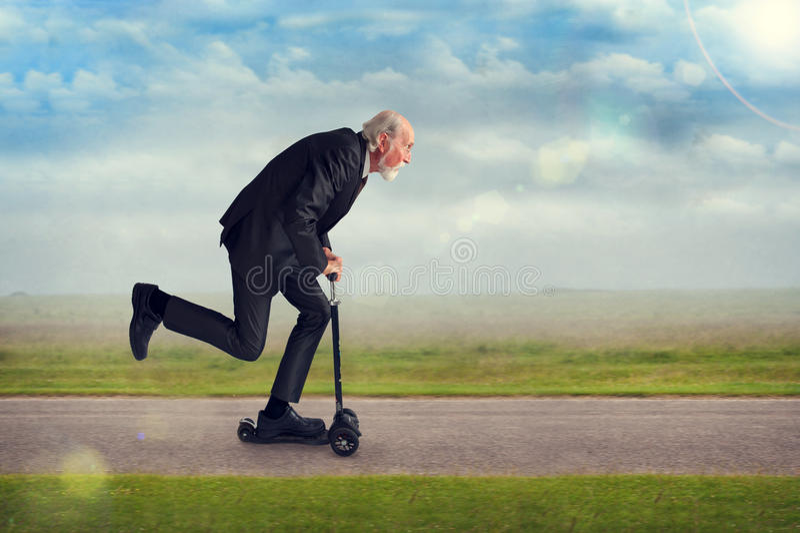 Hombre mayor que monta una vespa imagenes de archivo