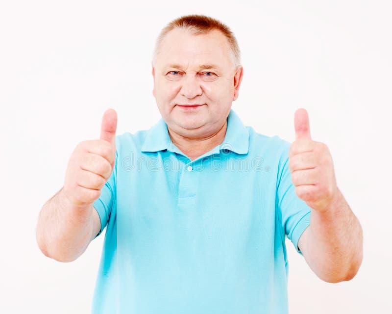Hombre mayor que muestra los pulgares para arriba sobre blanco imagenes de archivo