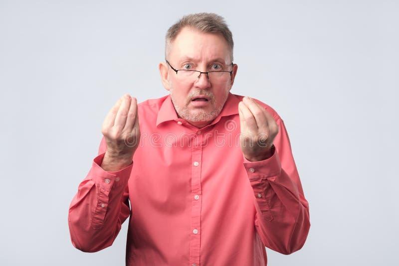 Hombre mayor que parece enojado mostrando gesto del italiano imagenes de archivo