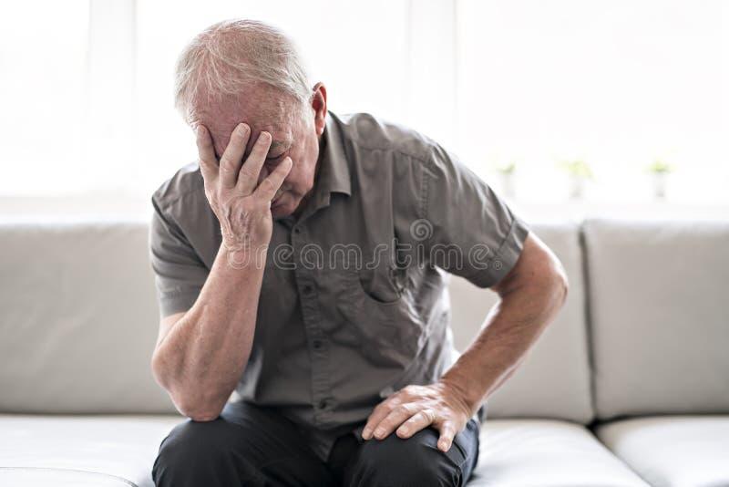 Hombre mayor que piensa y que se sienta en el sofá en casa como triste foto de archivo libre de regalías