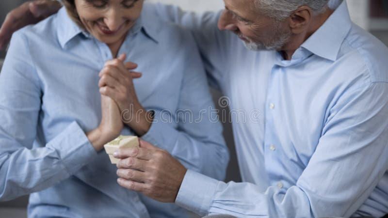 Hombre mayor que presenta el regalo a la esposa sorprendida feliz, celebrando aniversario imagen de archivo