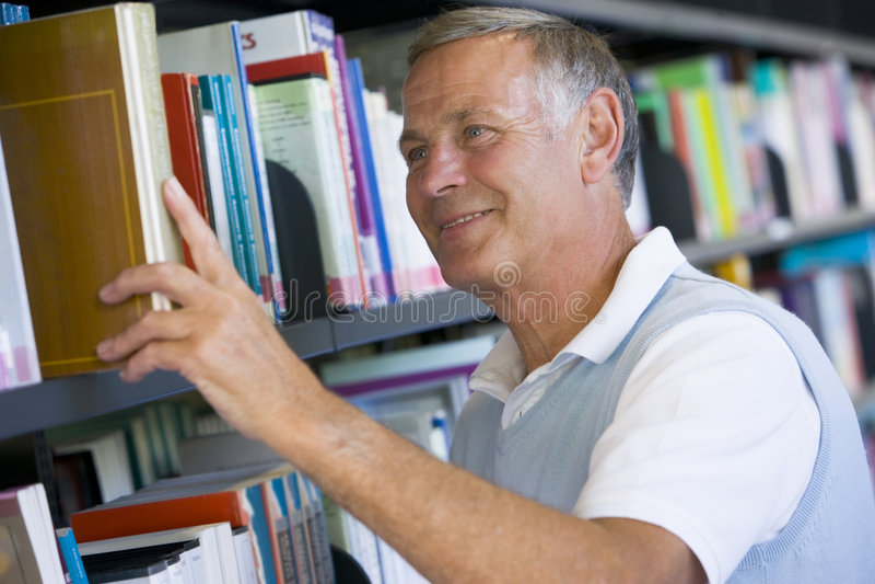 Hombre mayor que quita un libro de la biblioteca de estante imagen de archivo
