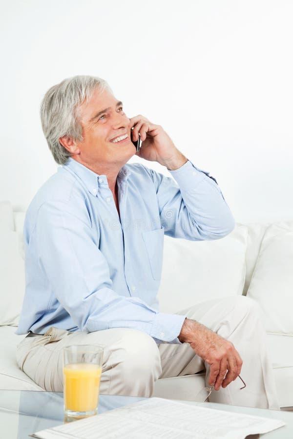 Hombre mayor que ríe en el teléfono imagen de archivo libre de regalías
