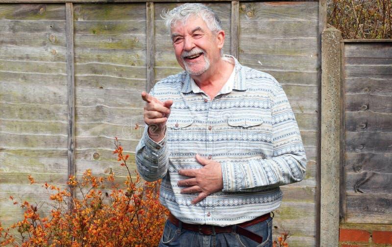 Hombre mayor que ríe y que señala. imagen de archivo