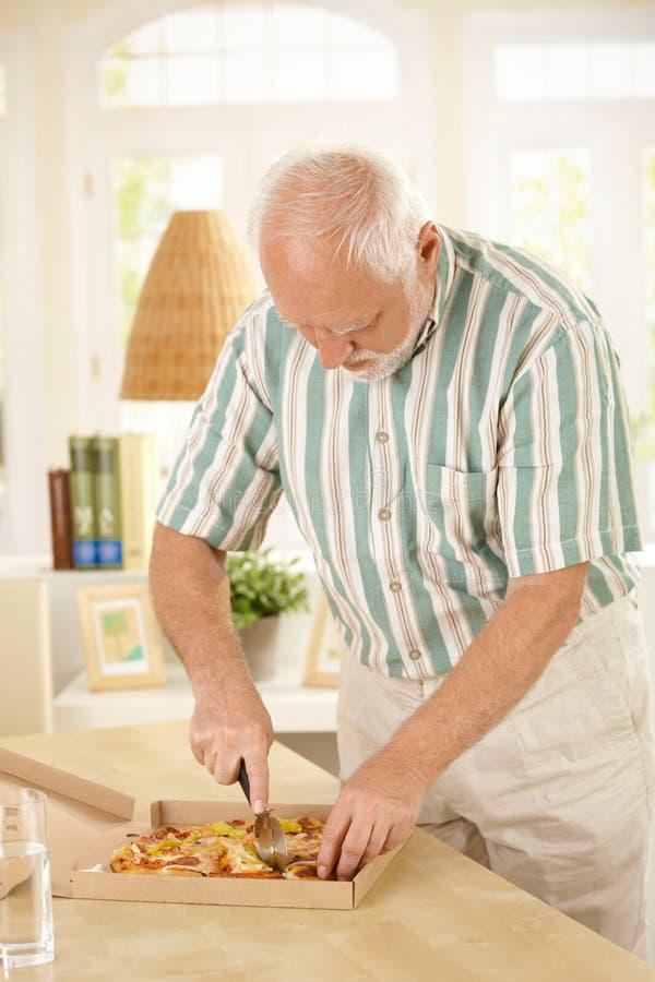 Hombre mayor que rebana encima de la pizza. fotografía de archivo
