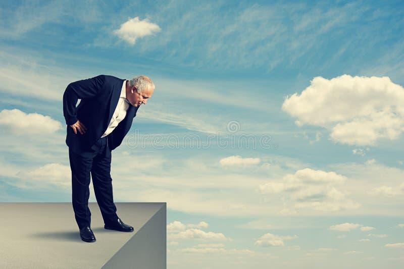 Hombre mayor que se coloca sobre el precipicio imagenes de archivo