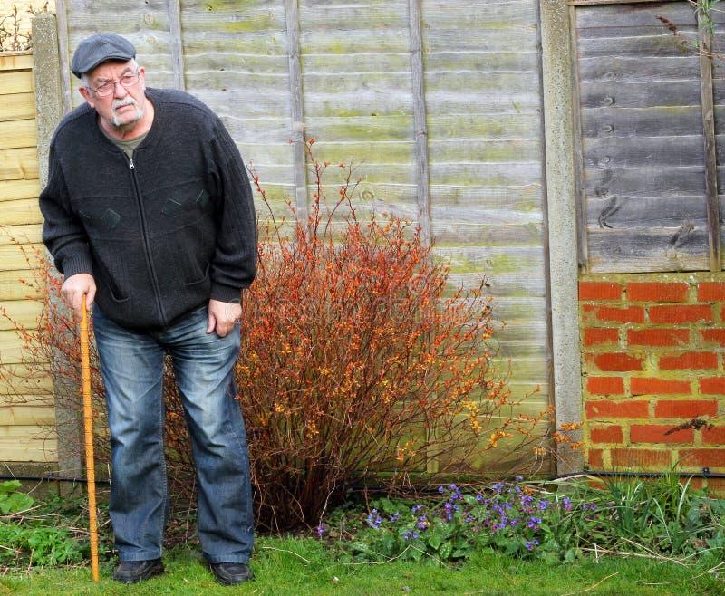 Hombre mayor que se coloca usando un palillo para la ayuda imagenes de archivo