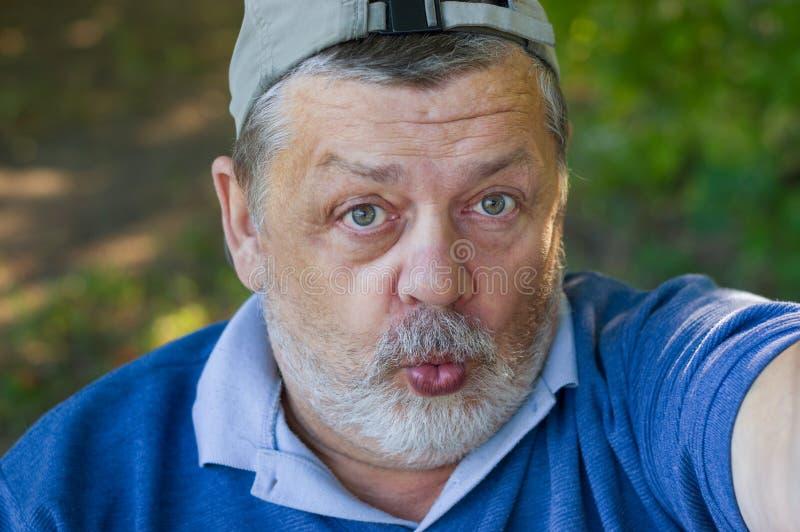 Hombre mayor que se pregunta y que hace el segundo selfie en su vida imagenes de archivo