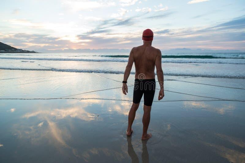 Hombre mayor que se prepara para nadar en el mar en el amanecer fotos de archivo