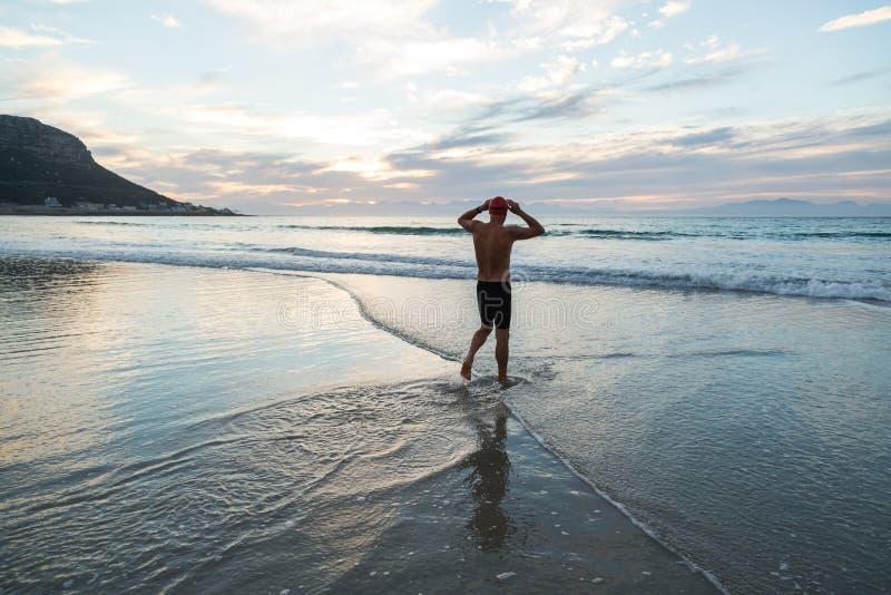 Hombre mayor que se prepara para nadar en el mar en el amanecer foto de archivo