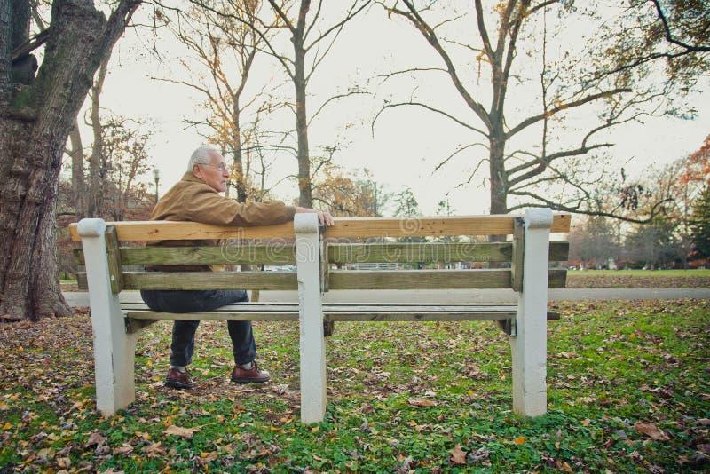 Hombre mayor que se relaja en banco foto de archivo
