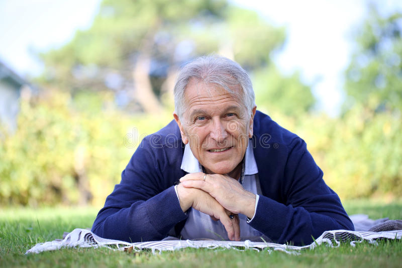 Hombre mayor que se relaja en hierba fotografía de archivo