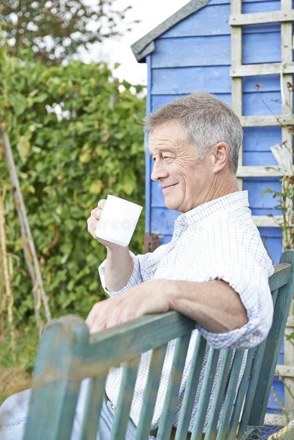 Hombre mayor que se relaja en jardín con la taza de café imágenes de archivo libres de regalías