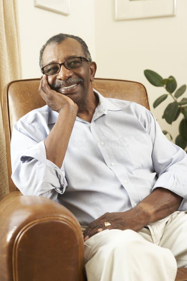 Hombre mayor que se relaja en silla en el país imagen de archivo