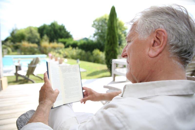 Hombre mayor que se relaja y que lee fotografía de archivo