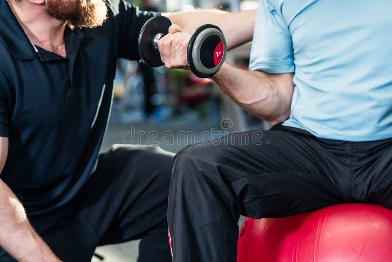 Hombre mayor que se resuelve con el instructor personal en el gimnasio fotos de archivo