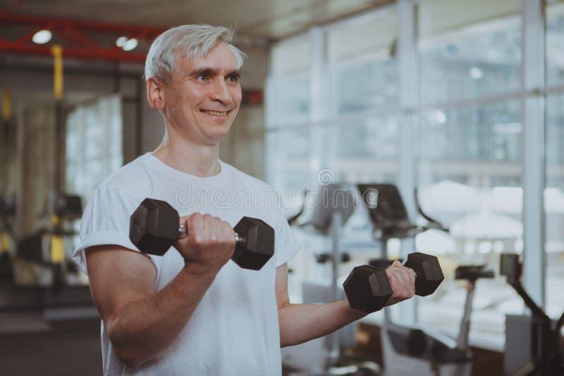 Hombre mayor que se resuelve en el gimnasio imagen de archivo