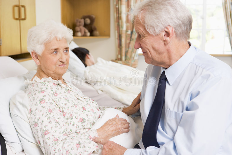 Hombre mayor que se sienta con su esposa en hospital imagen de archivo