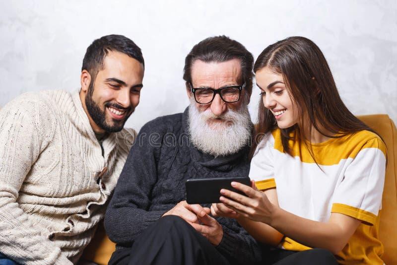 Hombre mayor que se sienta con sus niños imagen de archivo