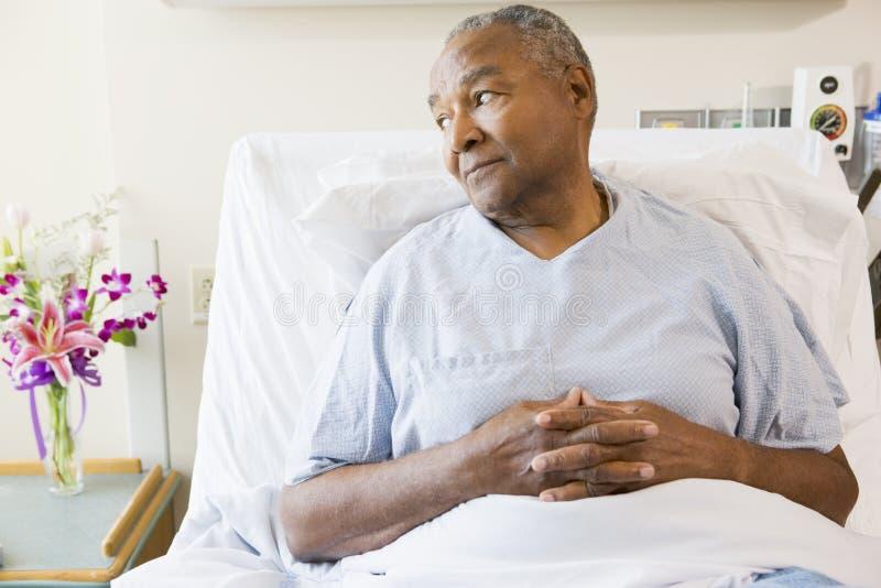 Hombre mayor que se sienta en cama de hospital imágenes de archivo libres de regalías