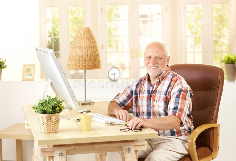 Hombre mayor que se sienta en el escritorio en casa foto de archivo libre de regalías