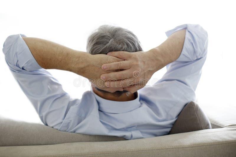 Hombre mayor que se sienta en el sofá que se relaja foto de archivo