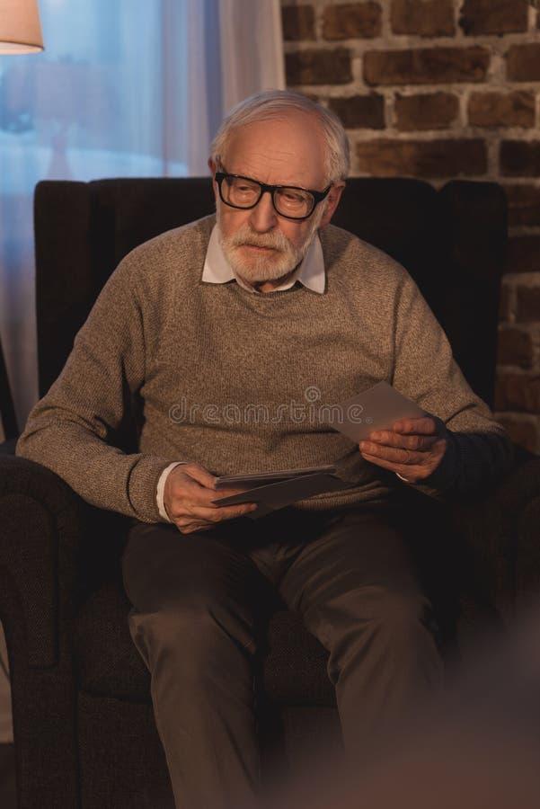 hombre mayor que se sienta en la butaca que sostiene las fotos viejas fotografía de archivo