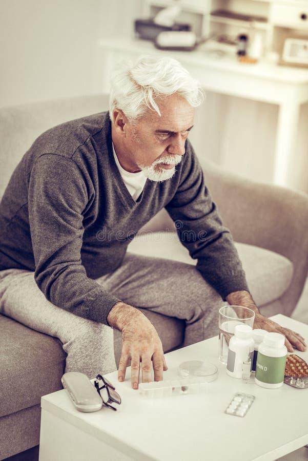 Hombre mayor que se sienta en la tabla por completo de cajas de las píldoras fotografía de archivo