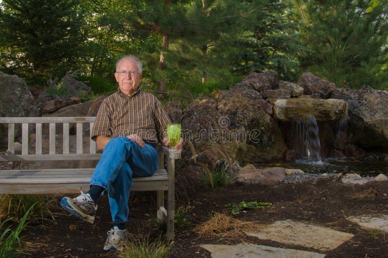 Hombre mayor que se sienta en un banco fotos de archivo