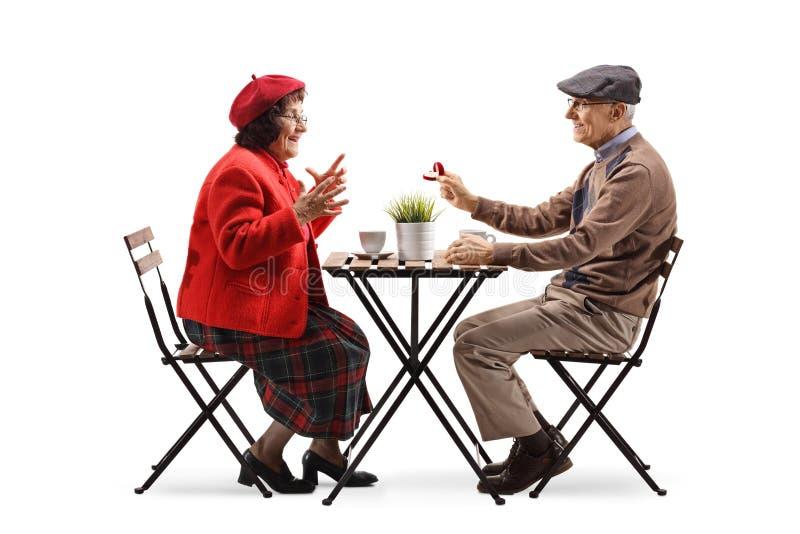 Hombre mayor que se sienta en un café y que da un anillo a una mujer mayor imagen de archivo