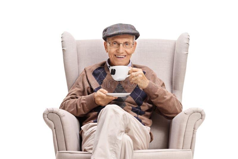 Hombre mayor que se sienta en una butaca y que bebe una taza de té fotos de archivo libres de regalías