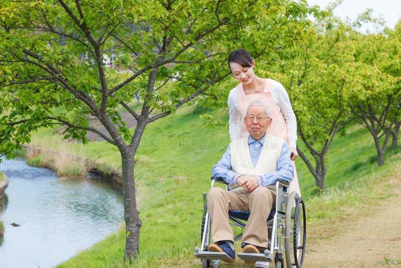 Hombre mayor que se sienta en una silla de ruedas con el cuidador imagen de archivo