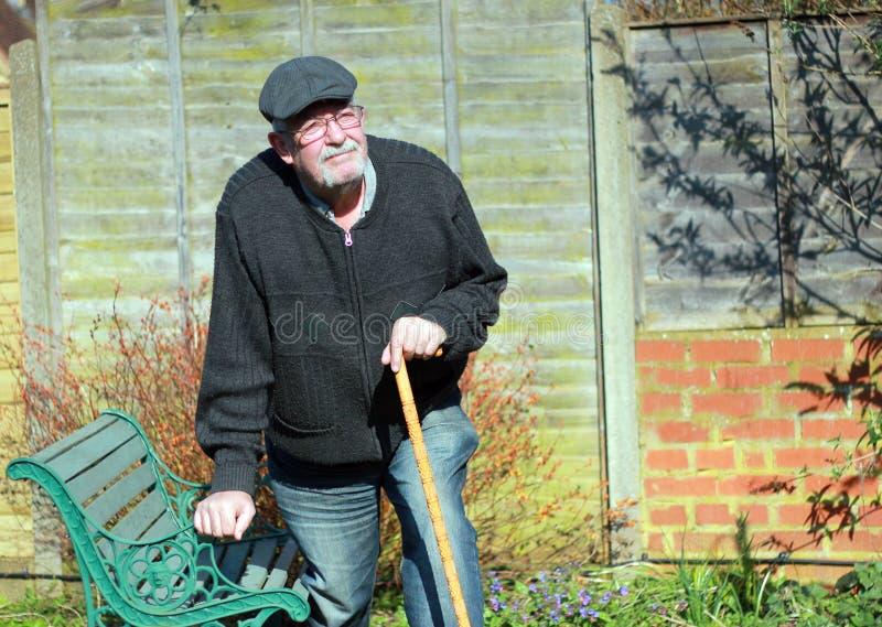 Hombre mayor que se sostiene sobre un banco para la ayuda fotos de archivo libres de regalías
