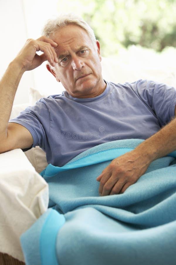 Hombre mayor que siente la reclinación mal debajo de la manta fotos de archivo