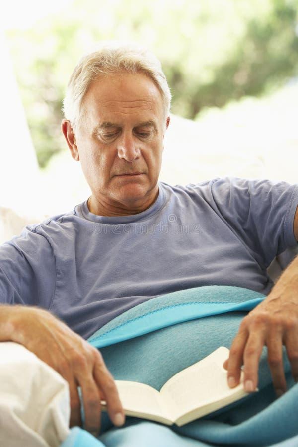 Hombre mayor que siente la reclinación mal debajo de la manta imagen de archivo