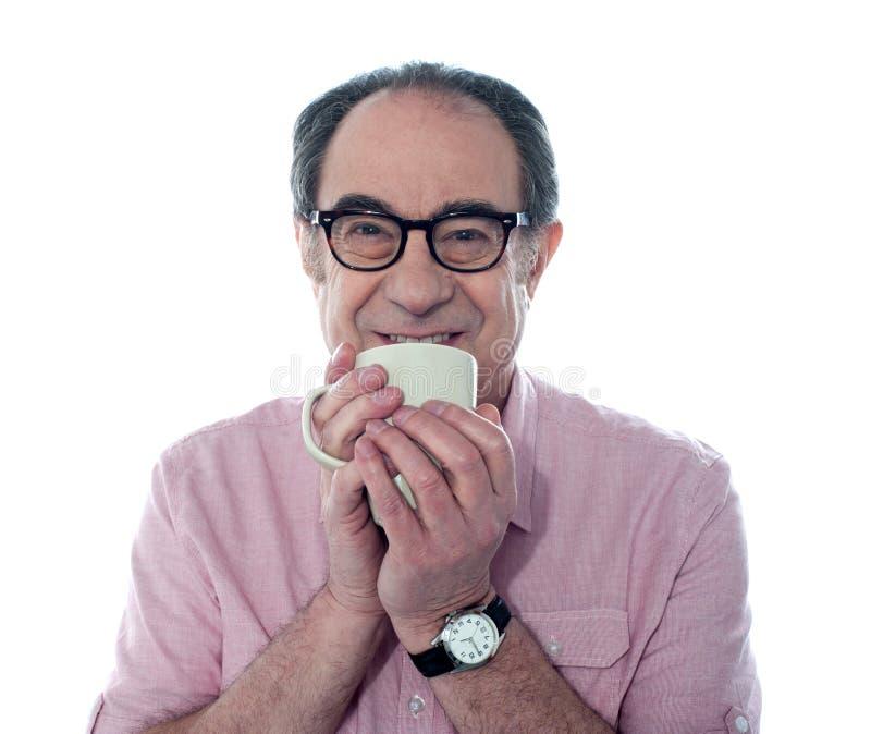 Hombre mayor que sonríe y que goza del café imagen de archivo