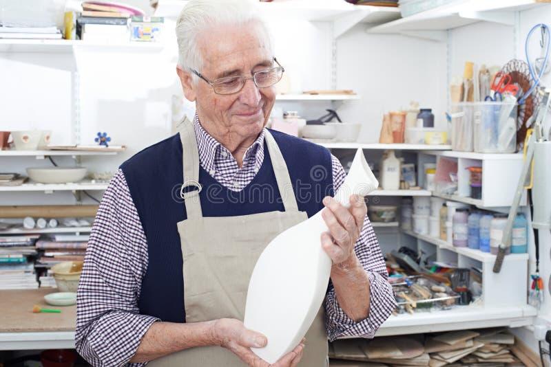 Hombre mayor que sostiene el florero en estudio de la cerámica imagen de archivo