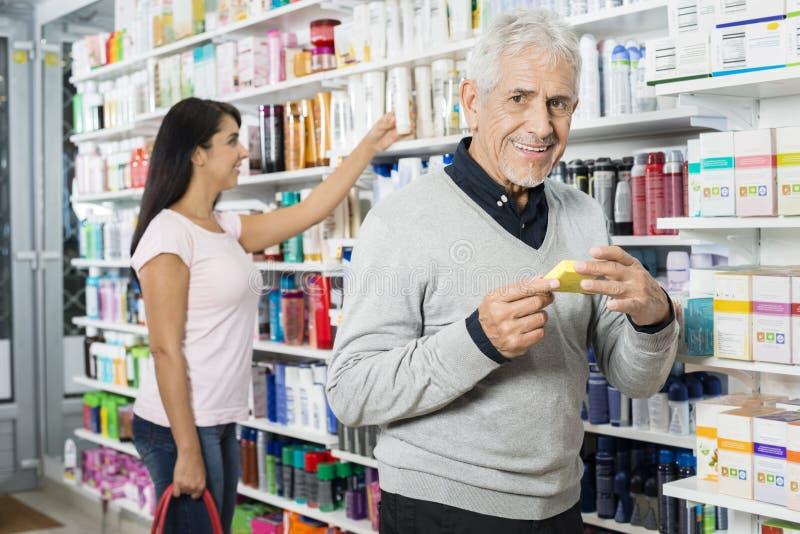 Hombre mayor que sostiene el producto mientras que compras de la mujer en farmacia fotos de archivo libres de regalías